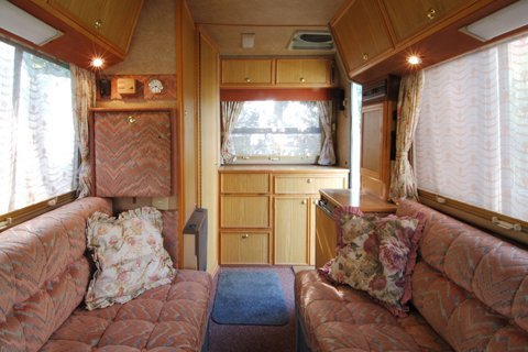 Inside view of a small caravan with red furniture