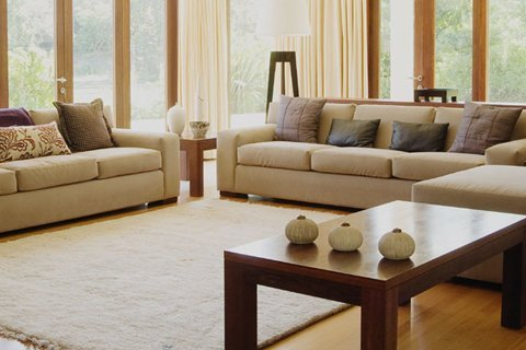 Corner cream sofa in home with oak floor and cream rug